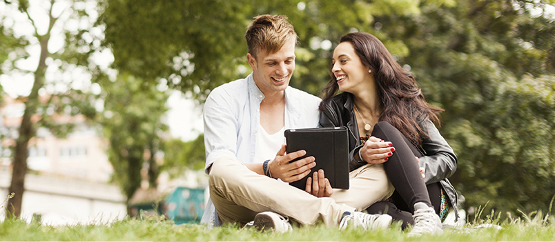 Young man and woman sit together outside, holding a tablet device and smiling.
