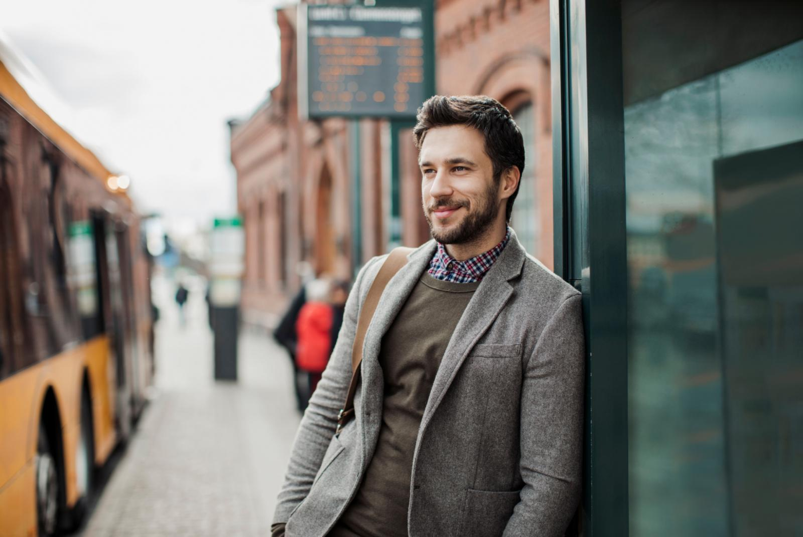 Man with a beard standing casually at a bus stop