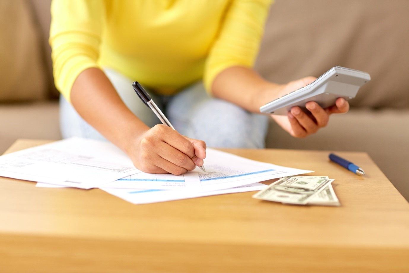 Woman holding calculator and planning a budget