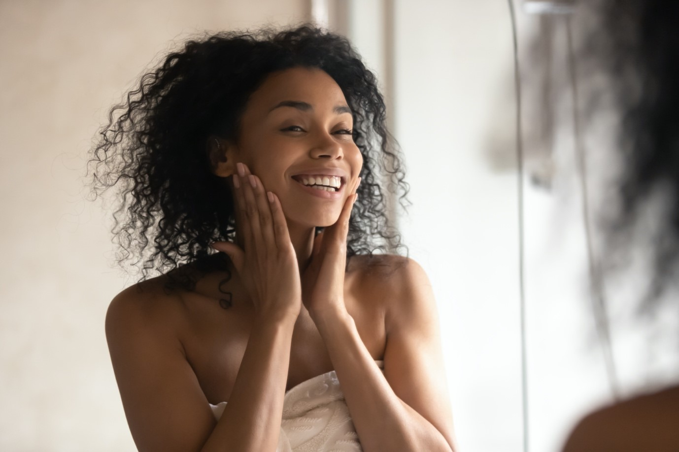 Woman in towel smiles in mirror after a shower