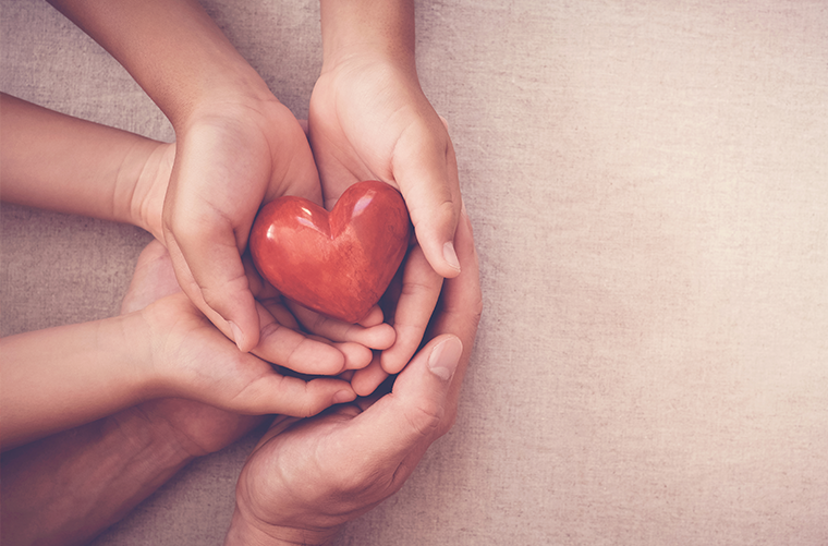 Adult hands cupping child's hands holding a heart-shaped red stone