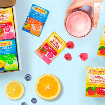 Packets of Emergen-C in different flavors resting beside fresh fruits and a glass of Emergen-C.
