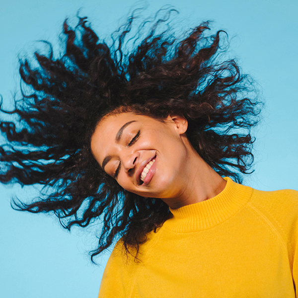 Young woman tossing her healthy hair.