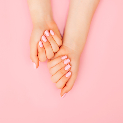 Nicely manicured hands against a pink background.