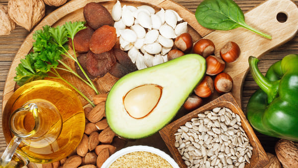 avocado, sunflower seeds, hazelnuts, and other foods rich in vitamin e on wooden plate