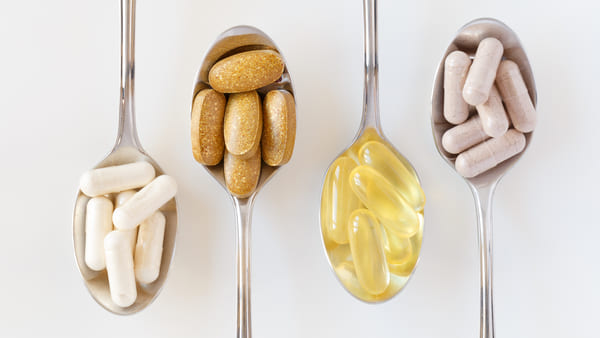 four spoons holding fish oil capsules, vitamins, and supplements with white background