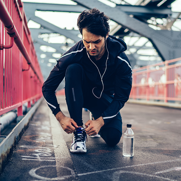 Man kneeling to tie his shoes while outside on a run