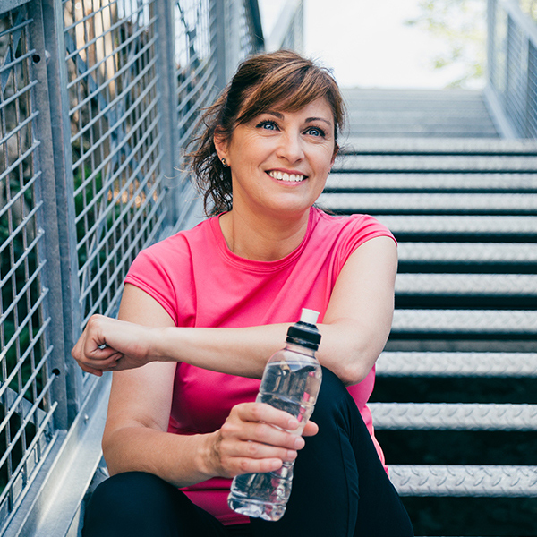 Smiling woman sitting on a stairway outside