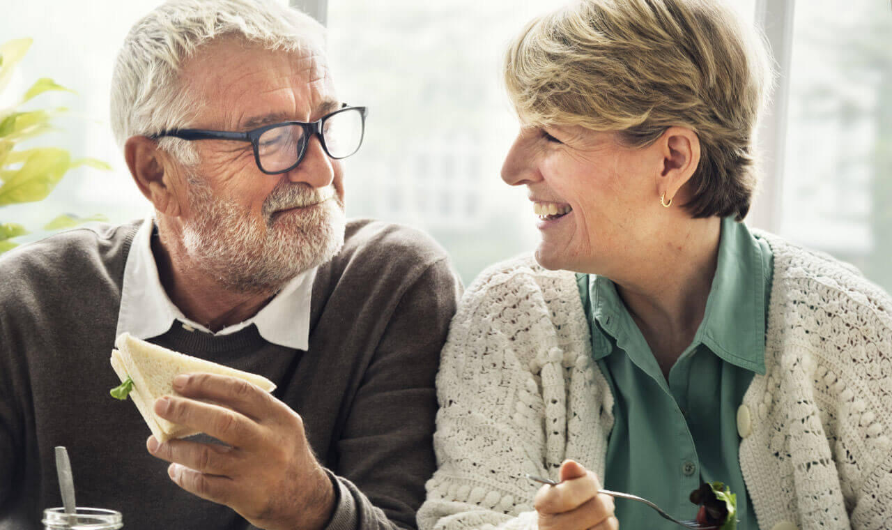 man and women enjoying some food with dentures and smiling at each other