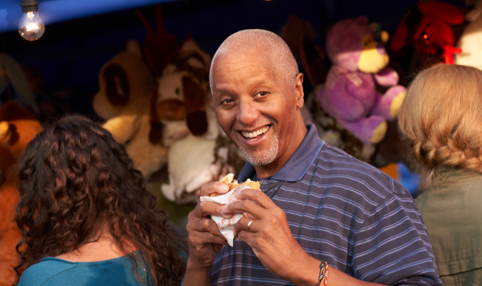 Smiling man holding a partly eaten burger at a town carnival