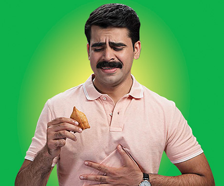 A man looking distressed while holding a samosa