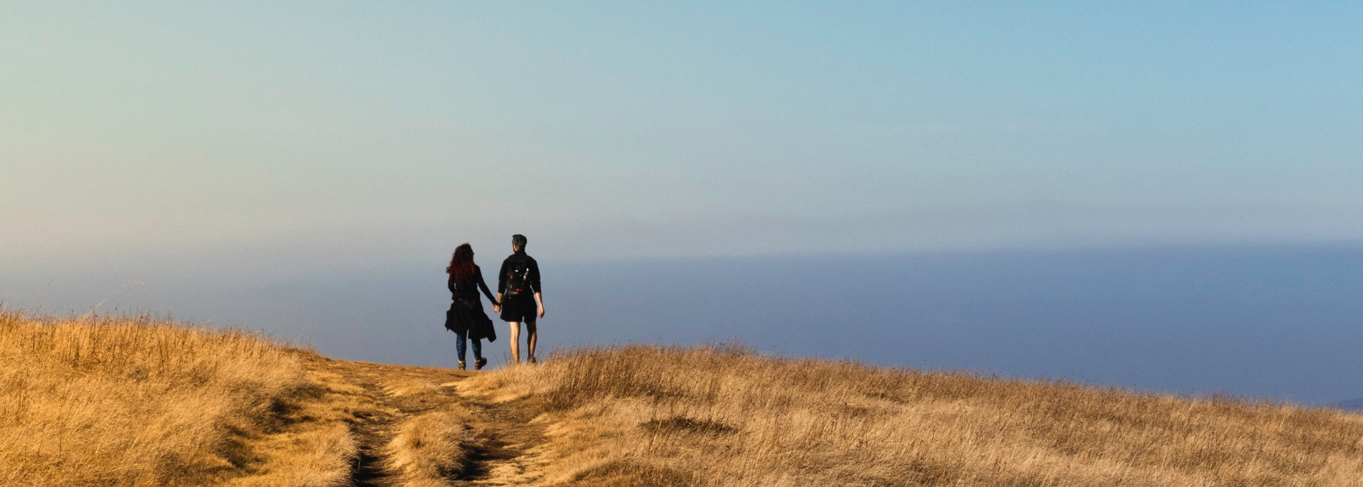 Boy and girl holding hands walking on yellow grassy plain with clear blue skies