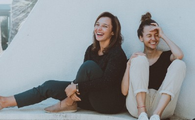 Two girls laughing on white concrete bench