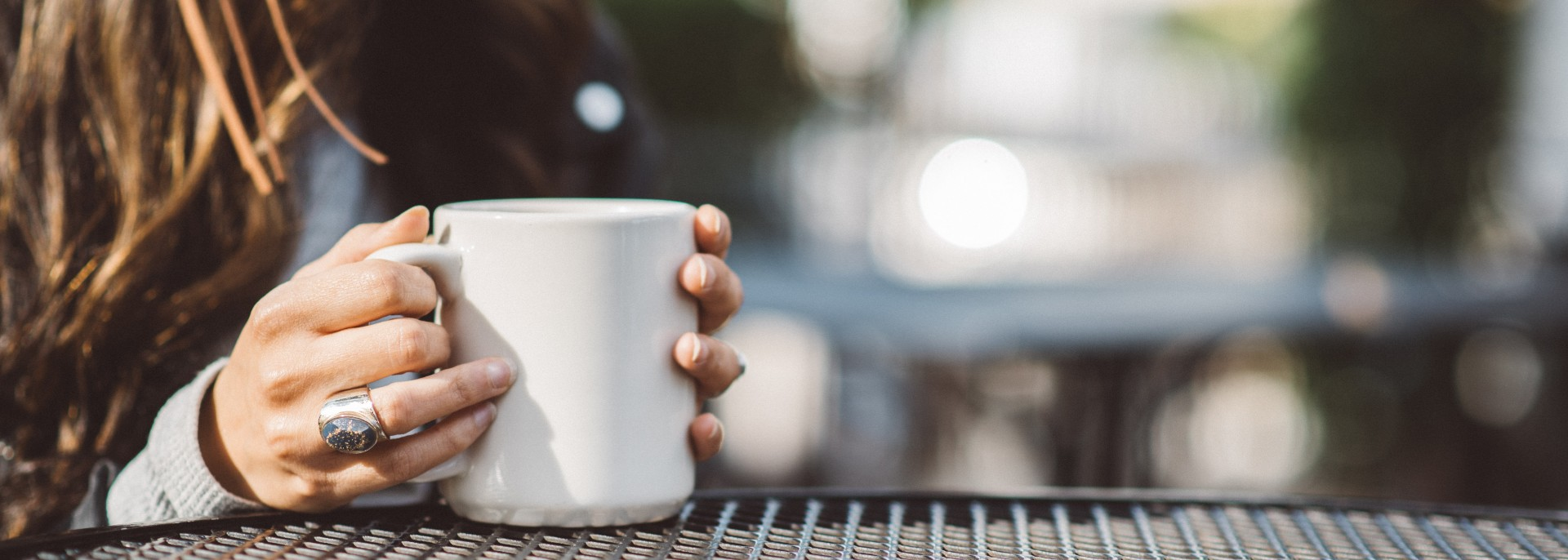 Girls hands holding a cup of coffee on grey table