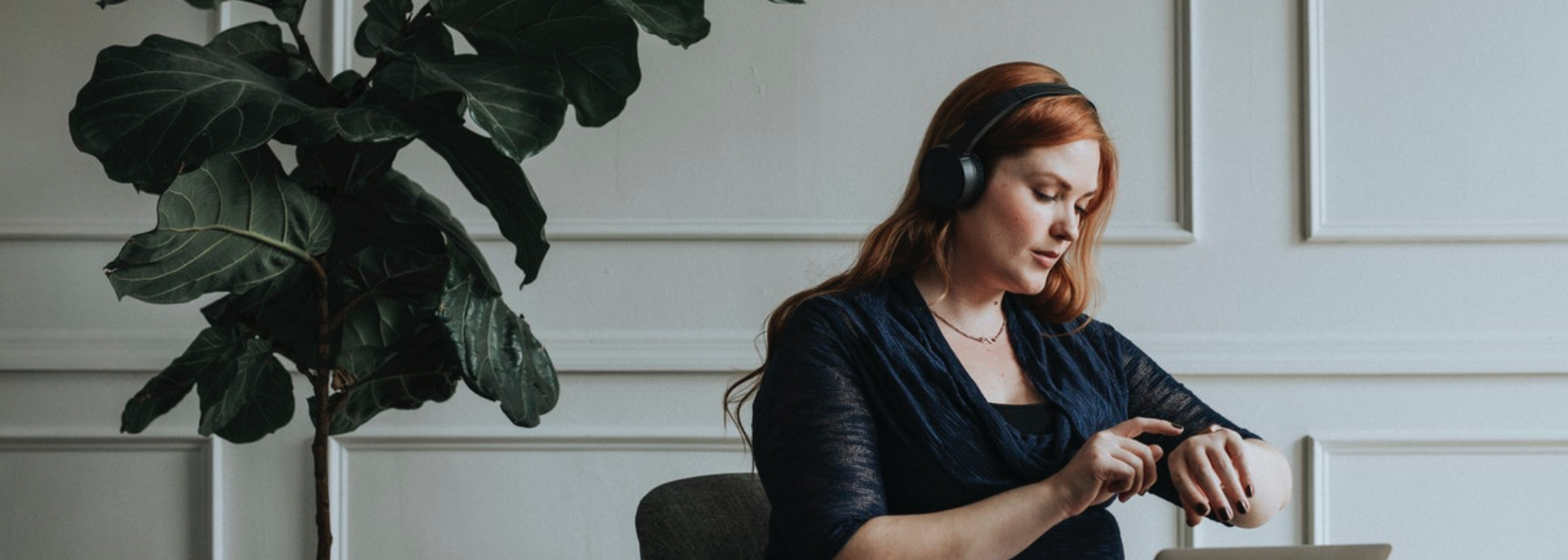 Girl seated, using a laptop with headphones on