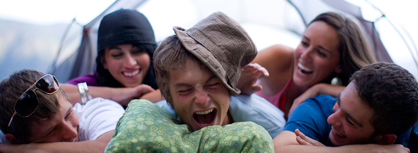 Friends Laugh As They Pile On Top Of Each Other During A Camping Trip