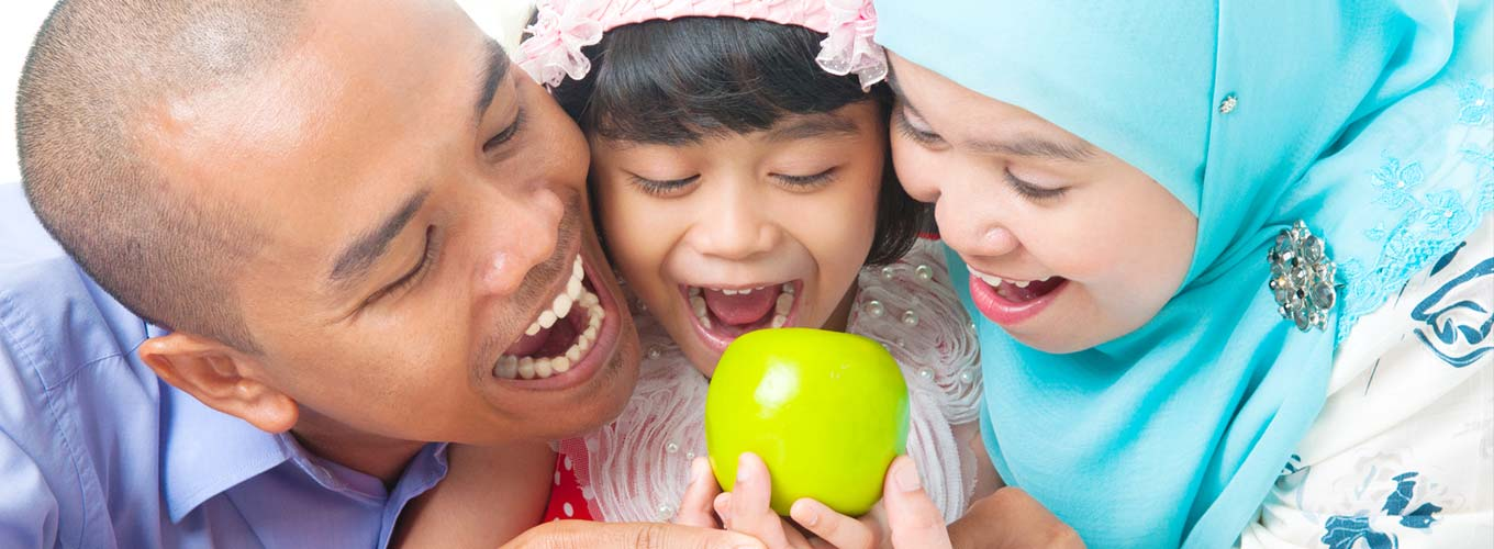 Father, mother and daughter getting ready to bite an apple