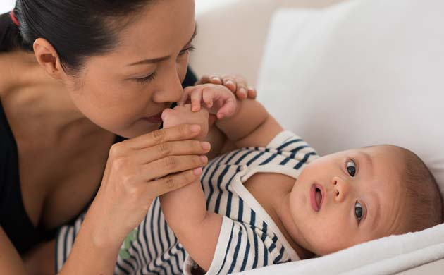 Mom Giving Kiss To Baby On Soft Bed