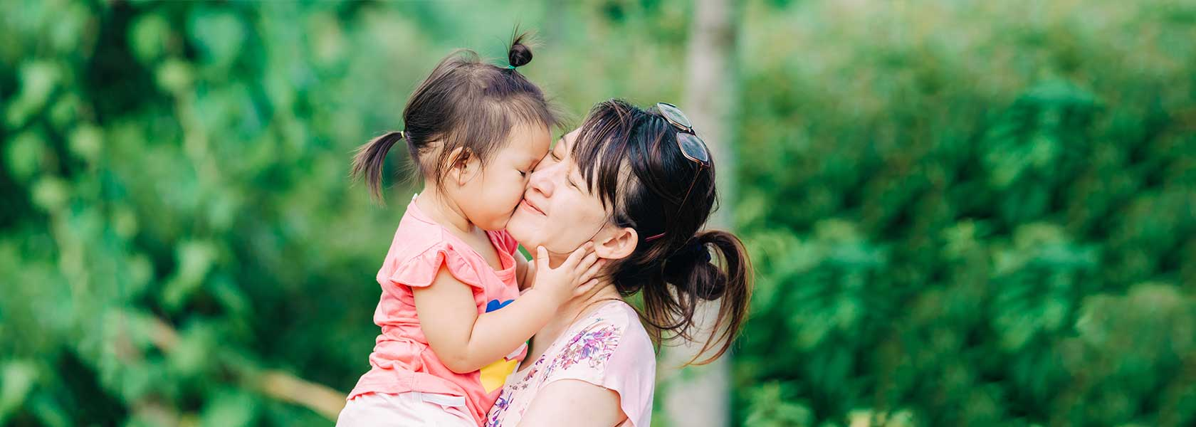 Mother carrying daughter in park