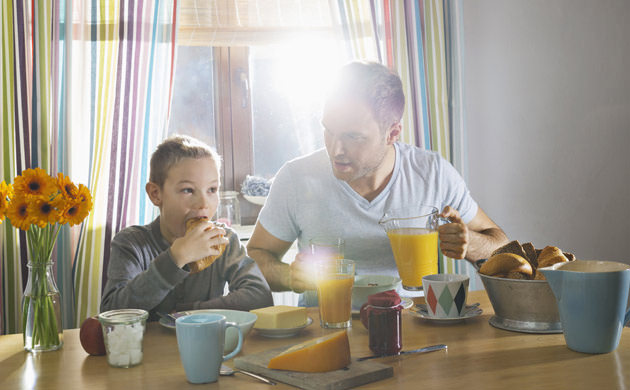 Father And Son Sitting At Breakfast Table