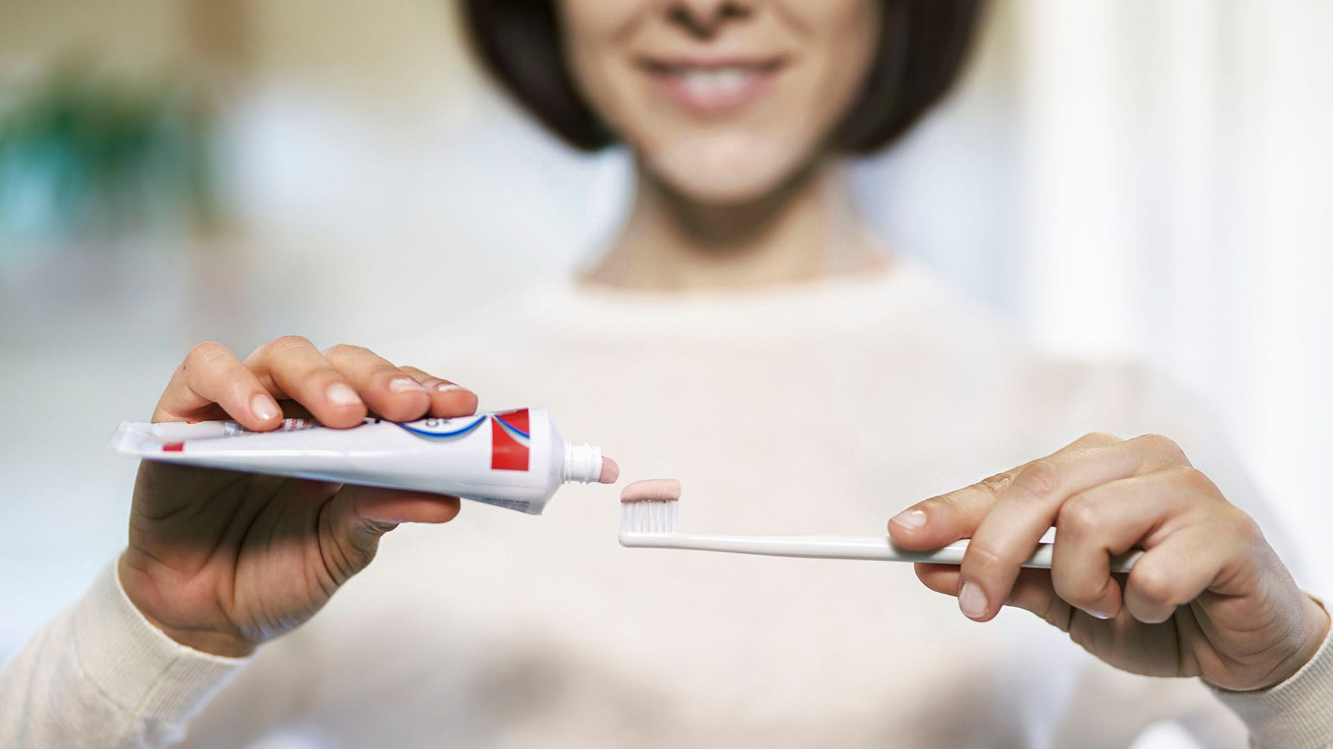 woman putting parodontax Complete Protection toothpaste onto a toothbrush