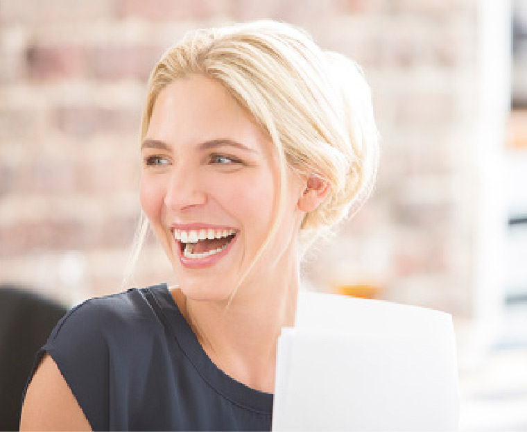 Woman smiling because she just finished whitening her sensitive teeth
