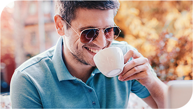 Man Holding A Cup of Coffee Smiling with White and Bright Teeth