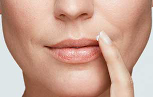 Close up of a woman pointing to a cold sore on her lips.
